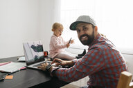 Father working from home, using laptop with his gaughter sitting on the desk, playing - JRFF02009