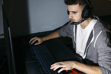 Young man sitting at his PC, playing computer games - JRFF02012