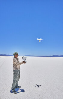 Bolivia, Salar de Uyuni, man flying drone on salt lake - SSCF00017