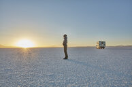 Bolivia, Salar de Uyuni, woman standing at camper on salt lake at sunset - SSCF00020
