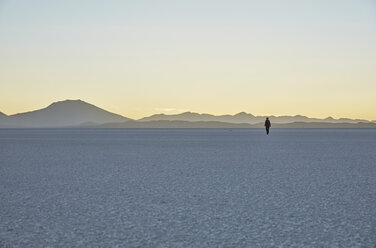 Bolivia, Salar de Uyuni, woman walking on salt lake at sunset - SSCF00023