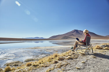 Bolivia, Laguna Colorada, woman sitting on camping chair at lakeshore using tablet - SSCF00029