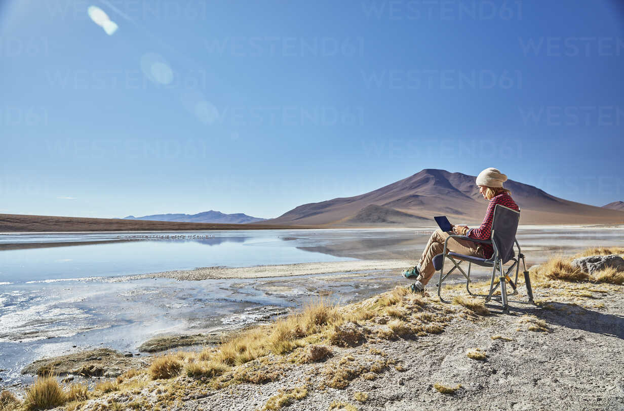 Bolivia, Laguna Colorada, woman sitting on camping chair at lakeshore using tablet - SSCF00029 - Stefan Schütz/Westend61