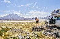 Chile, Salar del Carmen, man brushing his teeth at camper - SSCF00038