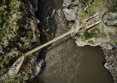 Peru, Quehue, aerial view of woman crossing rope bridge - SSCF00053