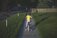 Rear view of girl riding bicycle on footpath at park - CAVF55875