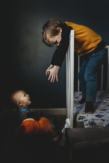 Boy gesturing to brother while standing in crib at home - CAVF55881