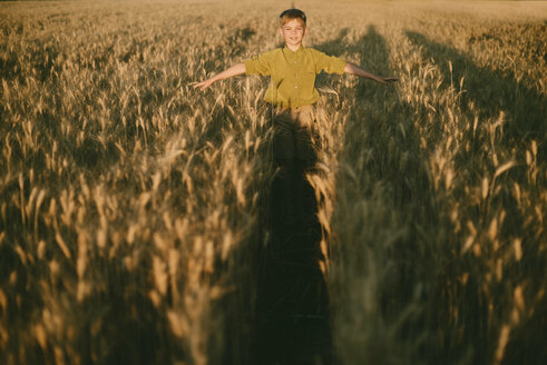Carefree boy with arms outstretched standing amidst wheat field during sunset - CAVF55905