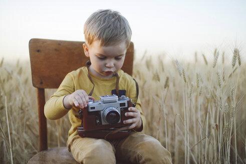 Cute boy with vintage camera sitting on chair amidst wheat field - CAVF55911