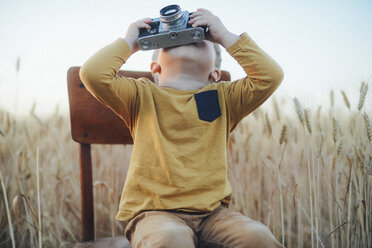 Playful boy photographing with vintage camera while sitting on chair amidst wheat field - CAVF55914