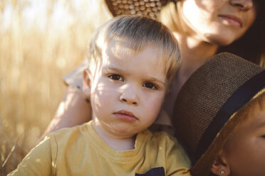 Portrait of cute boy with mother and brother on field - CAVF55917