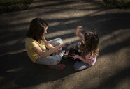 High angle view of sisters playing rock paper scissors game while sitting on road - CAVF55926