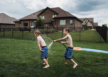Side view of shirtless boy spraying water on brother with garden hose at park - CAVF55929