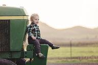 Cute baby boy sitting on tractor against clear sky - CAVF55941
