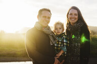 Portrait of smiling parents carrying son while standing against clear sky during sunny day - CAVF55944