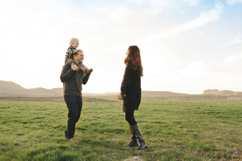 Father carrying son on shoulders while looking at wife on grassy field against sky - CAVF55947
