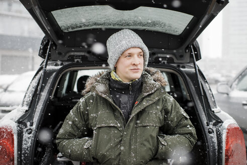 Man looking away while standing by car trunk during snowfall - CAVF55980