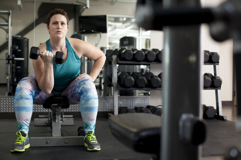 Full length of curvy woman lifting dumbbell while sitting on bench in gym - CAVF56010