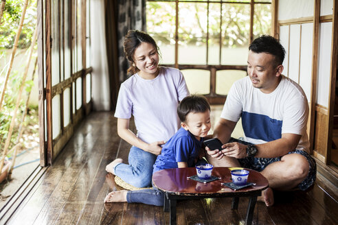 Japanese woman, man and little boy sitting on floor on porch of traditional Japanese house, drinking tea. - MINF09582