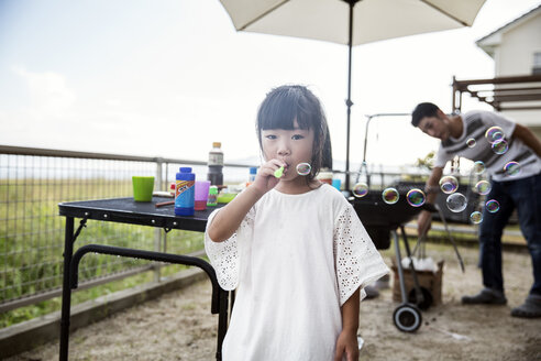 Portrait of Japanese girl wearing white shirt blowing soap bubbles. - MINF09597