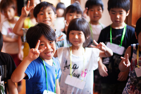 Group of smiling children in a Japanese preschool, making peace sign, looking at camera. - MINF09624