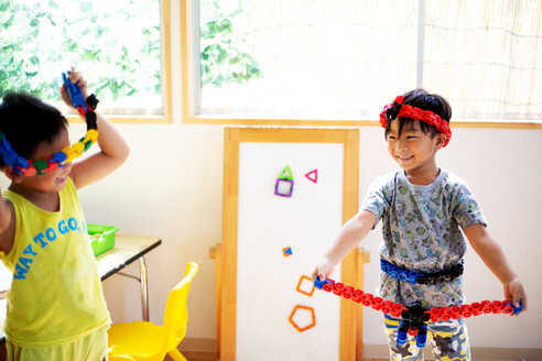Two smiling children playing with toys in a Japanese preschool. - MINF09636