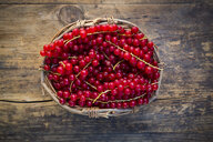 Red currants in basket on wood - LVF07561