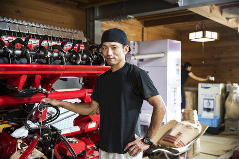 Japanese farmer wearing black cap standing next to agricultural machine, smiling at camera. - MINF09649