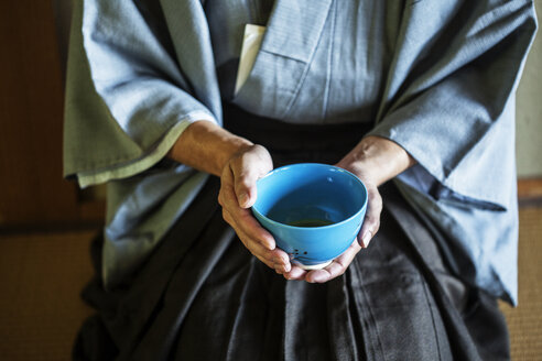 High angle close up of Japanese man wearing traditional kimono kneeling on floor holding blue tea bowl during tea ceremony. - MINF09682