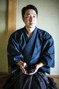 Japanese man wearing kimono kneeling on floor, holding tea bowl during tea ceremony. - MINF09688