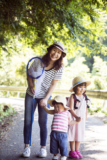 Smiling Japanese woman holding butterfly net and two girls wearing sun hats standing on path, looking at camera. - MINF09700