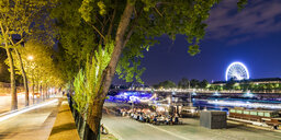 France, Paris, Champs-Elysees, Quai Anatole, people at River Seine bank at night - WDF04889