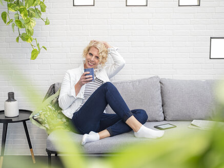 Portrait of smiling mature woman sitting on couch at home holding coffee mug - LAF02170