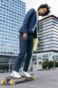 Spain, Barcelona, young businessman riding skateboard in the city - JRFF02037
