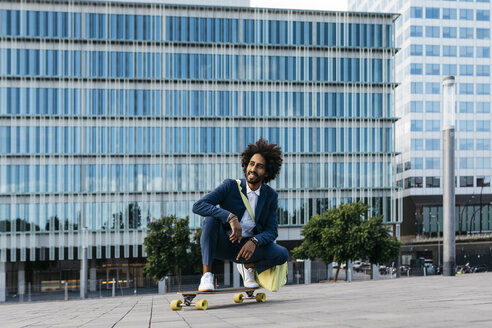 Spain, Barcelona, young businessman crouching on skateboard in the city - JRFF02040