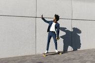 Young businessman riding skateboard along a wall taking a selfie - JRFF02049