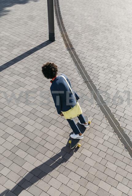 Young businessman riding skateboard on a square - JRFF02052 - Josep Rovirosa/Westend61