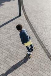 Young businessman riding skateboard on a square - JRFF02052