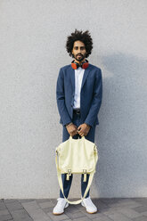 Portrait of stylish young businessman with bag and headphones at a wall - JRFF02058