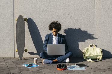 Young businessman sitting outdoors at a wall working on laptop - JRFF02061