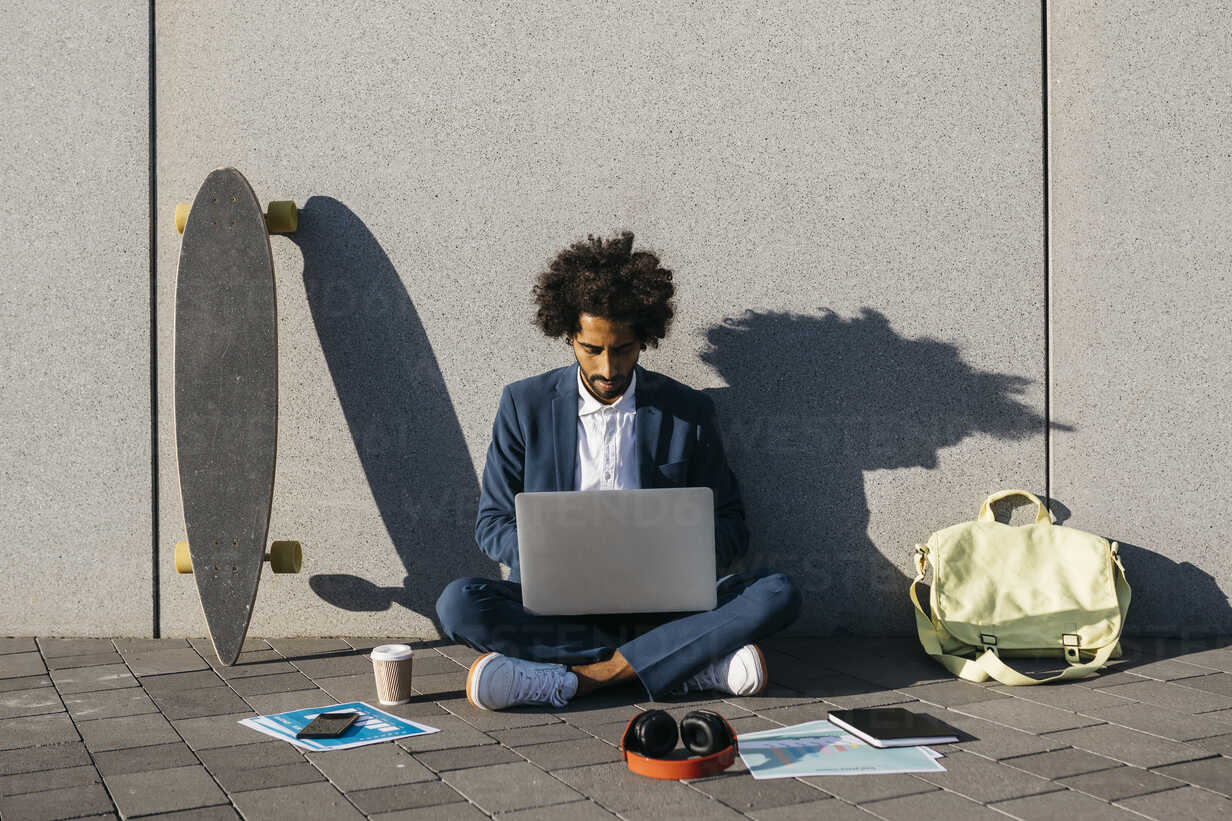 Young businessman sitting outdoors at a wall working on laptop - JRFF02061 - Josep Rovirosa/Westend61