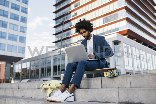 Spain, Barcelona, young businessman sitting outdoors in the city working on laptop - JRFF02064 - Josep Rovirosa/Westend61