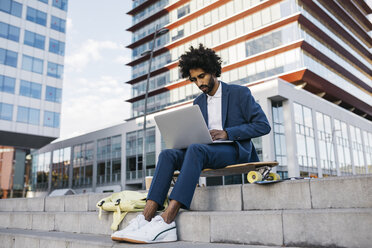 Spain, Barcelona, young businessman sitting outdoors in the city working on laptop - JRFF02064