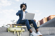 Spain, Barcelona, young businessman sitting outdoors in the city using cell phone and laptop - JRFF02067