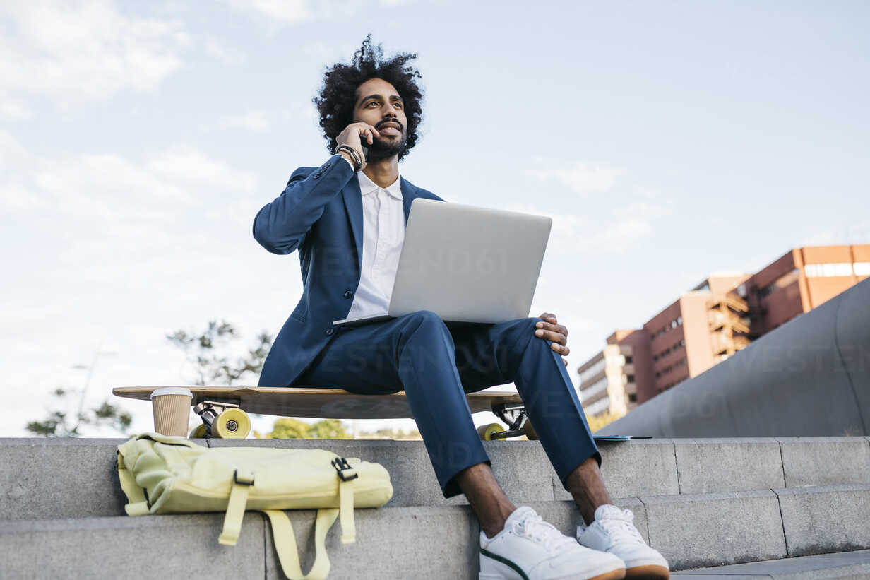 Spain, Barcelona, young businessman sitting outdoors in the city using cell phone and laptop - JRFF02067 - Josep Rovirosa/Westend61