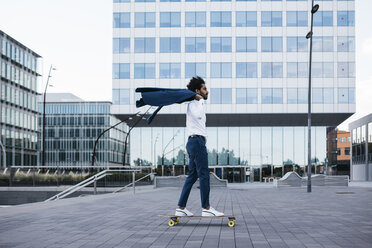 Spain, Barcelona, young businessman riding skateboard in the city - JRFF02076