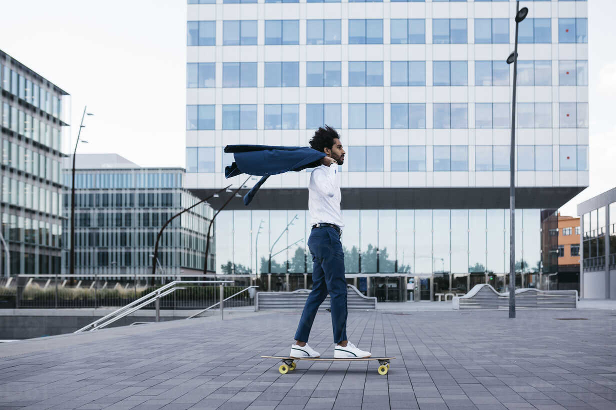 Spain, Barcelona, young businessman riding skateboard in the city - JRFF02076 - Josep Rovirosa/Westend61