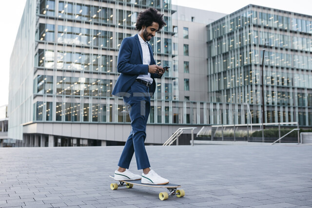 Spain, Barcelona, young businessman riding skateboard and using cell phone in the city - JRFF02079 - Josep Rovirosa/Westend61
