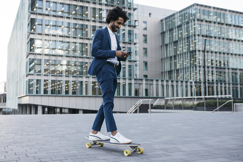 Spain, Barcelona, young businessman riding skateboard and using cell phone in the city - JRFF02079
