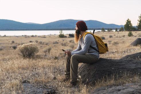 USA, North California, bearded young man having a break on a hiking trip near Lassen Volcanic National Park - KKAF02989